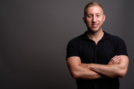 Man with blond hair wearing black polo shirt against gray backgr