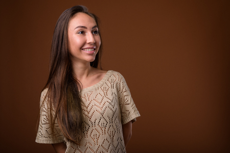 Studio shot of young beautiful woman against brown background