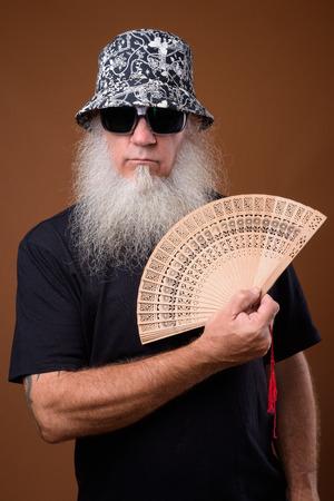 Uomo maturo con una lunga barba grigia su sfondo marrone