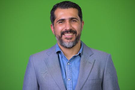 Hübscher persischer bärtiger Geschäftsmann gegen grünen Hintergrund