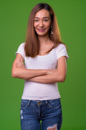 Young slim Asian woman against green background Banco de Imagens