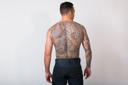 Portrait Of Shirtless Man With Tattoos Against White Background 写真素材
