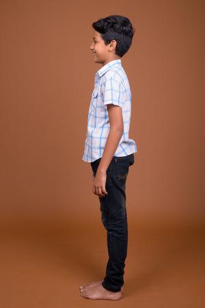 Młody indyjski chłopiec ubrany w kraciastą koszulę przed brązowym backgroun