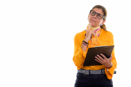 Studio shot of mature beautiful businesswoman holding clipboard
