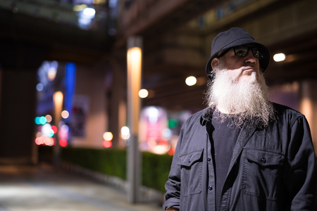 Mature bearded tourist man waiting in the city streets at night