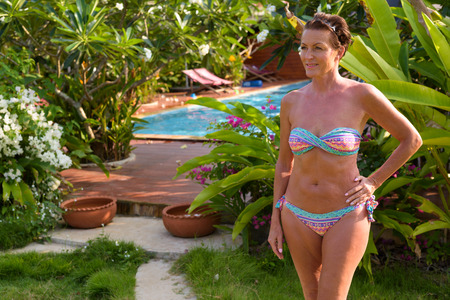 Mature beautiful tourist woman wearing bikini at the resort