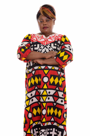 Studio shot of fat black African woman standing with arms crosse