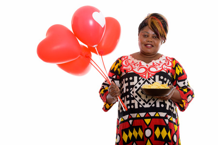 Happy fat black African woman smiling while holding bowl of pota