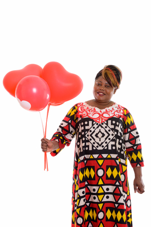 Studio shot of happy fat black African woman smiling while holdi