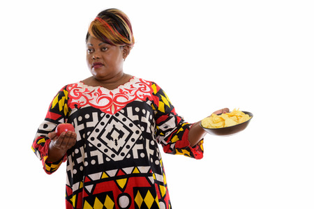 Studio shot of fat black African woman holding red apple and loo Standard-Bild