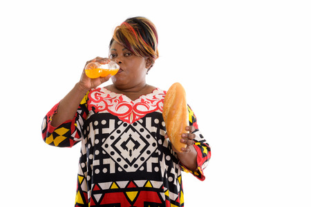 Studio shot of fat black African woman holding bread and drinkin