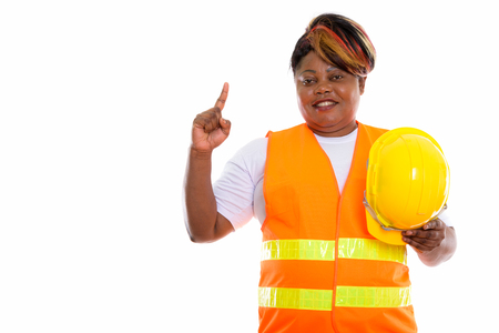 Studio shot of happy fat black African woman construction worker