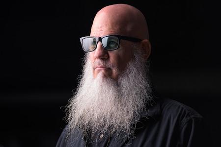 Portrait Of Bald Man With Gray Beard Thinking Outdoors At Night Standard-Bild