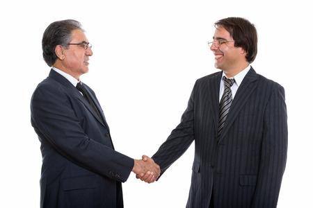 Profile view of happy young and senior Persian businessman smili Standard-Bild