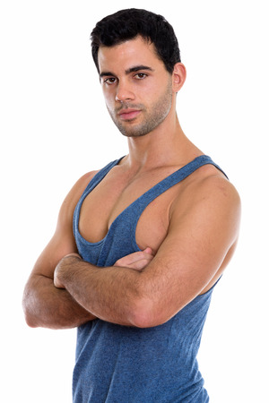 Studio shot of young handsome Hispanic man with arms crossed