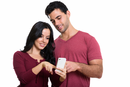 Studio shot of young happy couple smiling while using one mobile Stockfoto