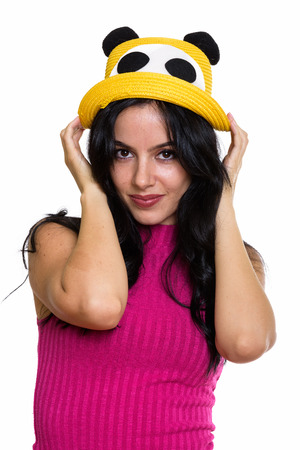 Studio shot of young beautiful Spanish woman holding hat with bo