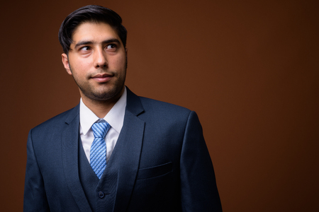 Young handsome Iranian businessman against brown background