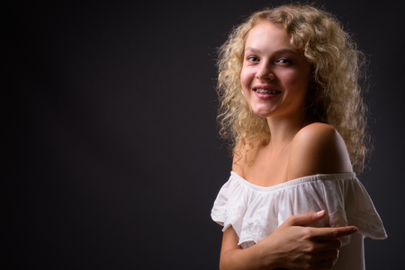 Young beautiful woman with blond curly hair against gray backgro
