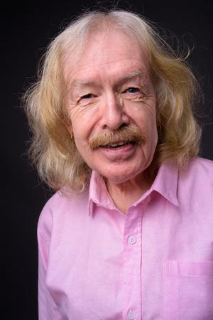 Senior businessman wearing pink shirt against gray background Banque d'images