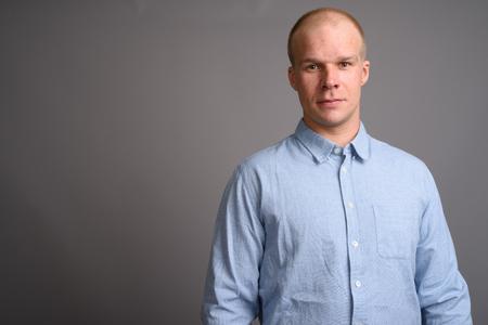 Bald businessman wearing blue shirt against gray background