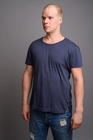 Bald man wearing blue shirt against gray background