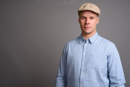 Finnish man wearing hat against gray background