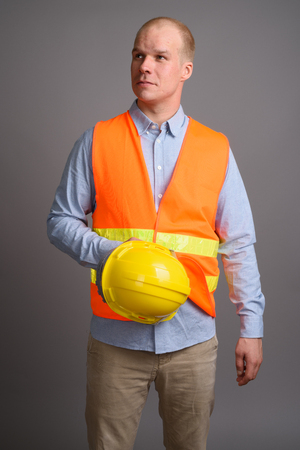 Bald man construction worker against gray background