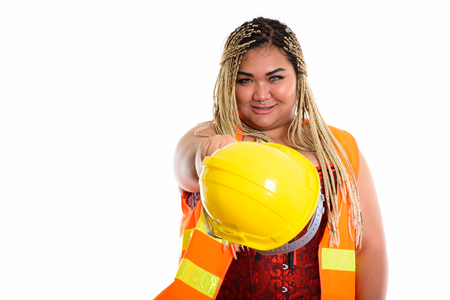 Young happy fat Asian construction woman smiling while pointing Standard-Bild