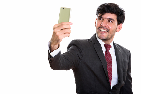 Young happy Persian businessman smiling while taking selfie pict Banco de Imagens