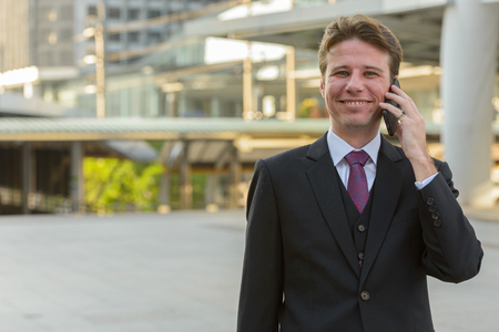 Happy businessman smiling and talking on mobile phone in front o