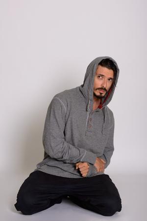 Studio shot of handsome man looking scared while kneeling