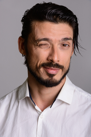 Face of handsome man winking against gray background