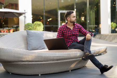 Young bearded Indian businessman relaxing at the mall in Bangkok