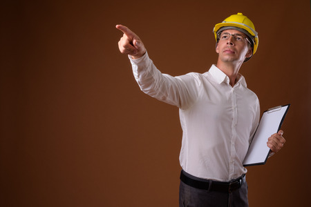 Portrait of businessman wearing hardhat against brown background
