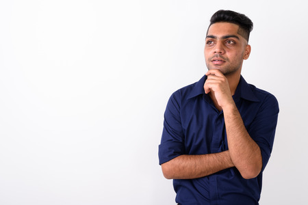 Studio shot of young Indian businessman against white background