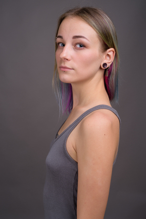 Young beautiful rebellious woman with multicolored hair against Stock Photo