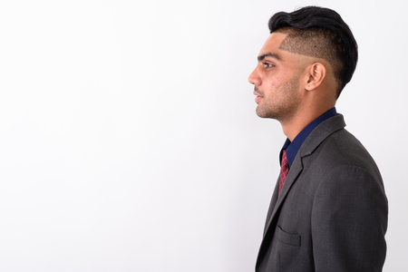 Young Indian businessman wearing suit against white background