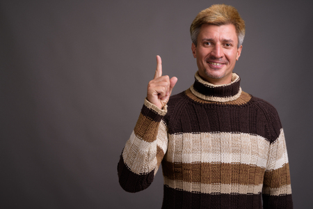 Man with blond hair wearing turtleneck sweater against gray back 版權商用圖片