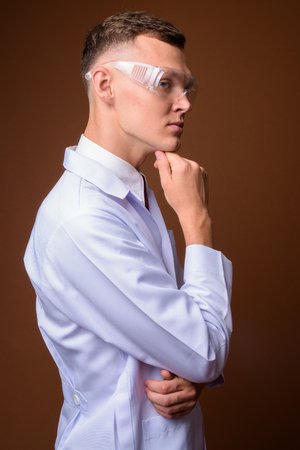 Young man doctor wearing protective glasses against brown backgr Banque d'images