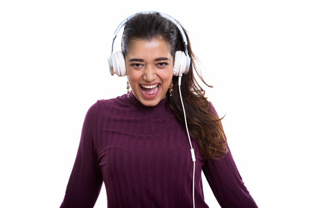 Young happy Indian woman smiling and shouting while listening to Stock Photo