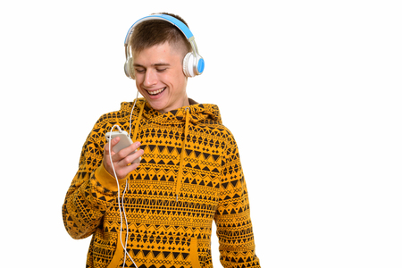 Young happy Caucasian man smiling while using mobile phone and l