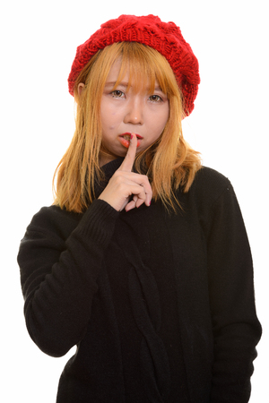 Young cute Asian woman with finger on lips