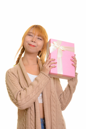 Young thoughtful Asian woman guessing gift box
