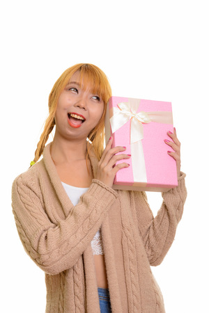 Young happy Asian woman smiling and guessing gift box