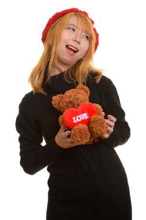 Young happy Asian woman smiling and holding teddy bear with hear Stock Photo