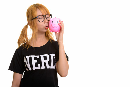 Young cute Asian nerd woman kissing piggy bank
