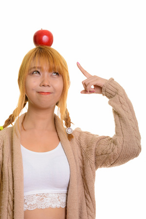 Young cute Asian woman with apple on head and pointing finger