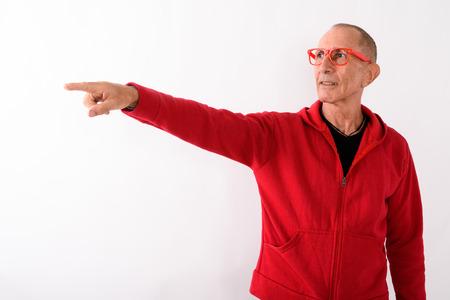 Studio shot of bald senior man pointing at distance while wearin