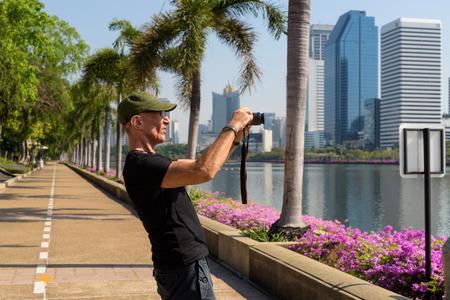 Profile view of senior tourist man wearing cap while taking pict